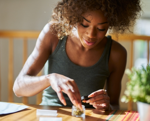 african american woman at home rolling marijuana joint from dispensary bought weed